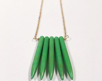 Green howlite sticks on gold.