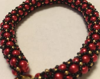 Stunning red pearl netted bracelet with black and gold bead trim