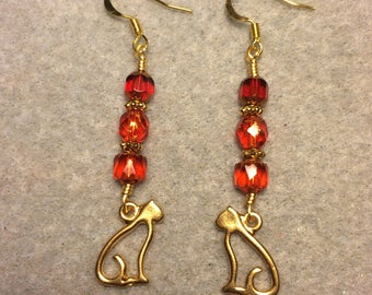 Gold cat charm dangle earrings adorned with red Czech glass beads.