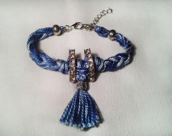 Handmade bracelet with braided strap in blue-white color with rhinestones and tassel.