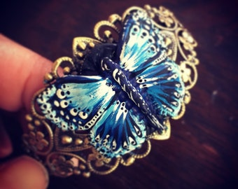 SOLD- Hand made Black Clay Butterfly Painted in Blue and White on an Adjustable Antiqued Brass Cuff By Brooke Baker