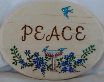 Peace wood burned plaque with inspirational message, decorated with blue birds a birdbath and blue flowers embellished with colored crystals