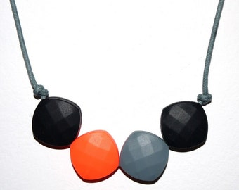 Teething necklace in black, neon orange and grey, made from BPA free chewable silicone quadrate beads by Little Gnashers
