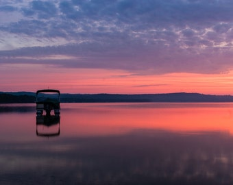 Sunset over Little Glen Lake with pontoon boat at Sleeping Bear Dunes, Michigan
