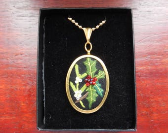 Necklace. Hand embroidered Holly and Mistletoe design on black fabric, gold colour necklace.