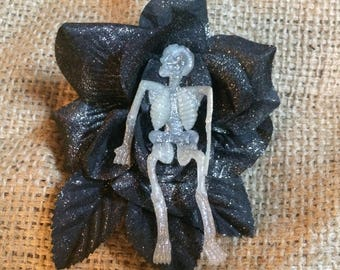 Black rose hair flower featuring a rubber skull in the center.