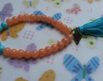 Cute salmon and blue glassbeads stretchy bracelet with a blue tassel and charm