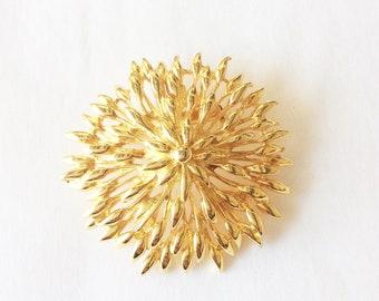 Sunburst brutalist design gold tone round domed brooch