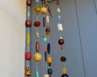 Mobile garden or patio with multicolored beads and drift wood.