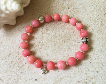 Charming pink coral stretch bracelet with decorative elements and a heart charm, natural stone bracelet