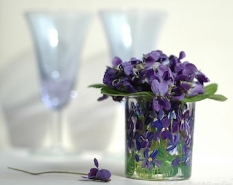 A small hand-painted glass flower vase with violets