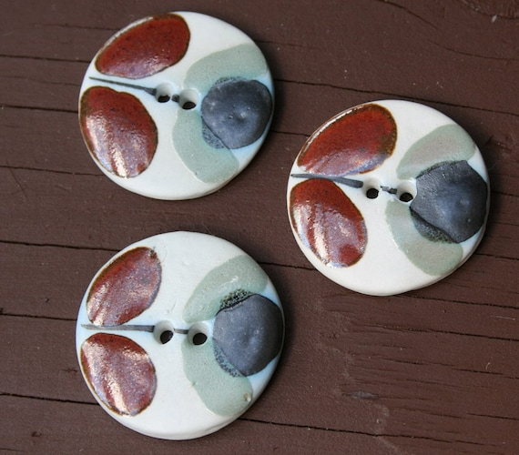 3 vintage handmade clay buttons with a rusty brown, navy and sage green pattern
