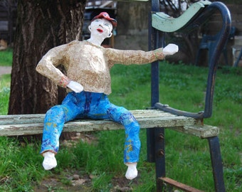A curious seated figure in papier-mâché