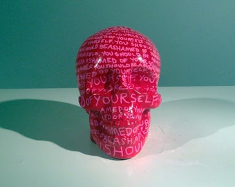 One of a kind human skull sculpture- casted, and hand painted with red and pink enamel