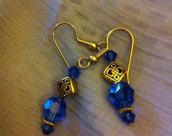 Blue sapphire and gold plated pierced earrings with Celtic knot beads.