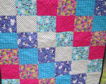 A happy doggy quilt!  A cute puppy quilt  done in colors of pink and purple, turquoise, polka dots, black and white, 34 X 42 inches