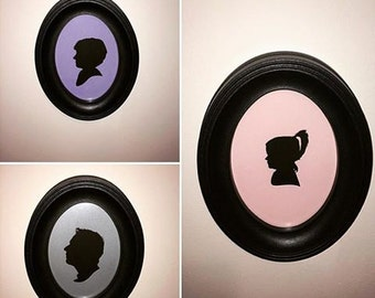 Single Custom Paper Cut Silhouette on Colourful Background Framed in Black Oval Frame