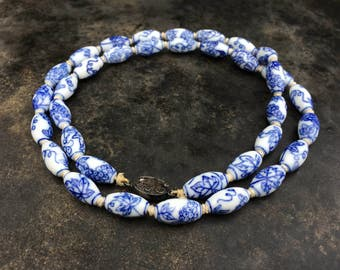 Chinese export necklace of blue and white painted porcelain beads, knotted on silk, with a silver filigree clasp.