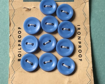 Eleven small vintage blue lingerie buttons on card