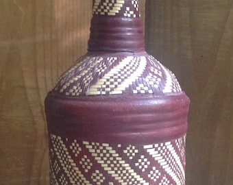 Glass bottle covered in a wickerwork of leather and rafia