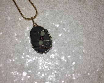 Black beach stone with gold wire wrapping,