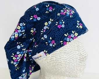 Traditional Bouffant Scrub Cap scrub hat featuring a dark blue material with flowers in pink blue white and yellow