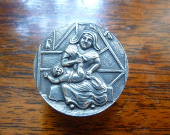 Button depicting mother and baby (late 1800's).