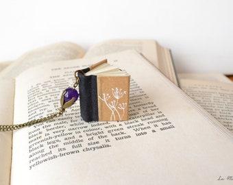 Collana con libro nero con fiori di tarassaco bianchi disegnati e pendente con perla viola . Regalo per scrittori, lettori e librai