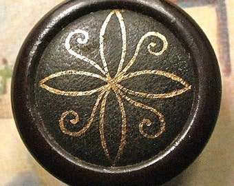 Leather button, vintage.  Embossed brown leather/gold design, slightly curved top, brown ptd. metal rim, 2 hole sew-thru. c1940's.