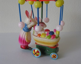 Antique Tin Wind Up Toy Momma Bunny pushing Baby Bunny in Basket Full of Easter Eggs - Has Red Carrousel that Turns - Made by OKD, Japan