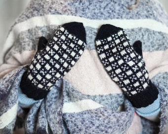 Woolen mittens knitted of natural black and white yarns