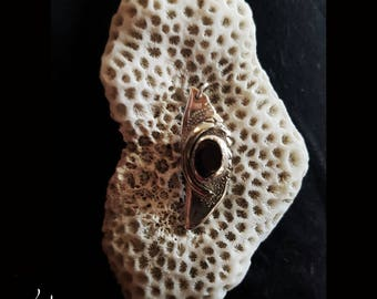 Sea berry : Artwork - A unique pendant, with a red garnet that glimmers red in the light. There is a pattern on the surface.