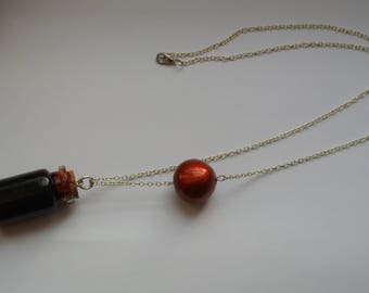 blood vial and metalisee red ball necklace