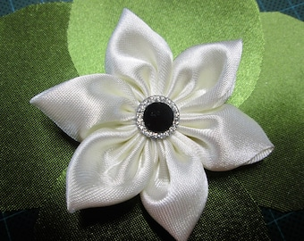 Ivory satin with a flower is adorned with a black button surrounded with glitter