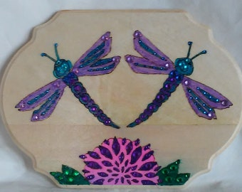 Dragonflies! wood burned plaque with colorful dragonflies over a pink flower on pine, embellished with colored crystals.