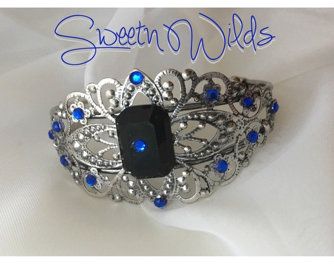 Vintage style antique cuff bracelet accented in sapphire-like gems.