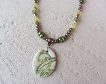 Oval Pendant and green metal and glass beads necklace the little ceramic raku green floral pattern