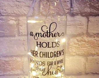 Message on a bottle with quote 'A mother holds her children's hands for a while & their hearts forever'.