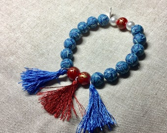 Bracelet blue iridescent beads and Red tassels