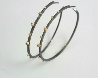 Oxidized silver and gold, hammered hoop earrings with two diamonds, studded gold granules and rough surface.