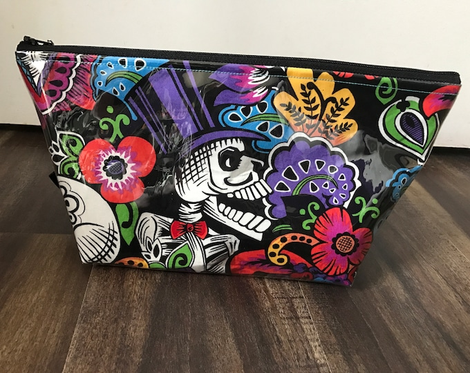 Zippered makeup bag in a sugar skull  fabric with clear vinyl top layer