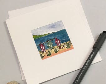 Hand painted blank card, three beach huts with bucket and spade. Free UK delivery.