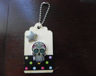 A wooden tag decorated with a skull colorful measuring 7 x 4 cm