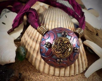 Polymer Clay - round dome pendant - Burgundy and blue raised pattern with bronze celtic medallion encased in resin.
