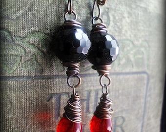 Rote und schwarze Kupferdraht umwickelt Ohrringe.