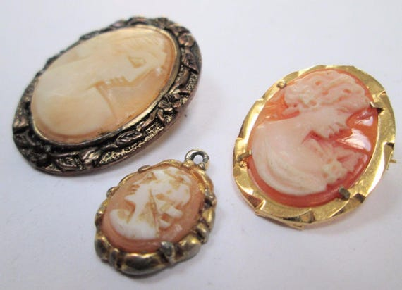 Two vintage gold metal & carved shell cameo brooches and pendant
