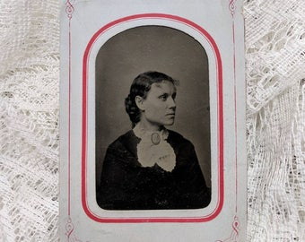 Tintype photograph of a beautiful fashionably dressed woman in a paper frame wearing a cameo brooch