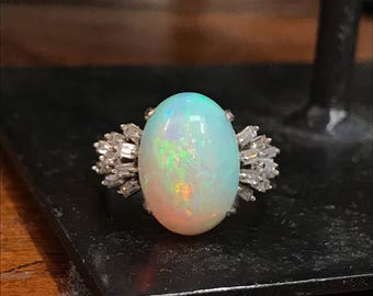 14k white gold fiery opal ring with approximately 1ctw banquette diamonds. Sz 7, 4.9dwt stone is approximately 10 x 15mm.
