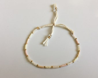Petite stretchy friendship bracelet in delicate colors and golden details