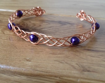 Copper Celtic cuff bracelet, with purple glass pearl beads.